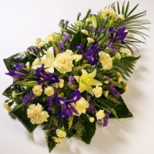 Lilies and Carnations are presented with Irises, Spray Carnations and luxury foliage to create this lemon and blue teardrop spray.