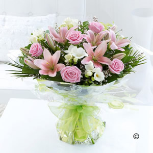 Pink roses, lilies arranged with fragrant white freesia