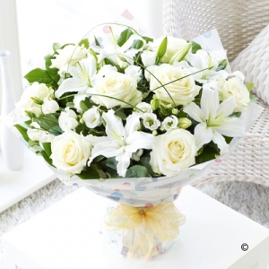 features white lilies, lisianthus and roses. Classically beautiful!