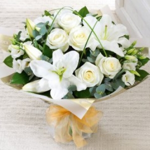 White lilies, roses and lisianthus expertly arranged in a hand tied bouquet