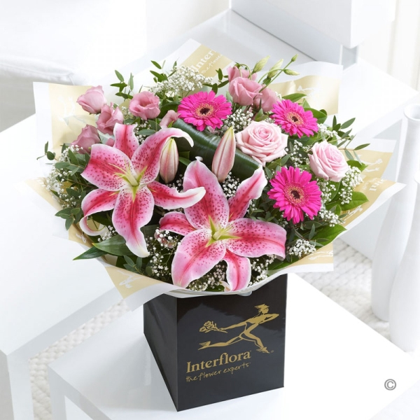 Pink lilies, germini, roses and lisianthus hand tied with white gyp.